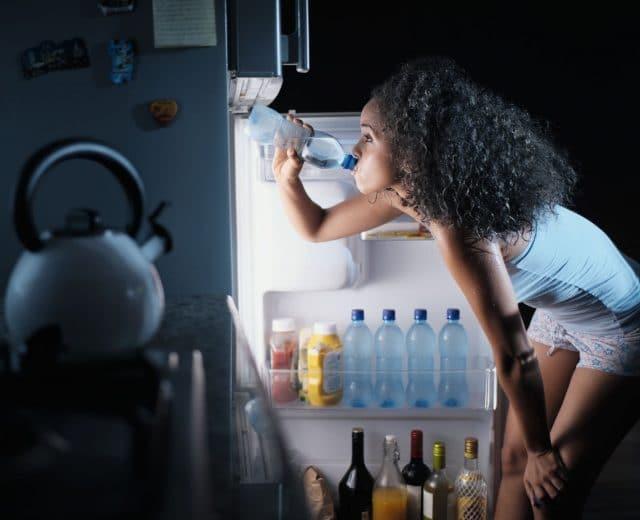 femme buvant eau froide du frigo