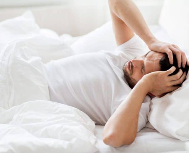 Homme ayant la migraine dans un lit